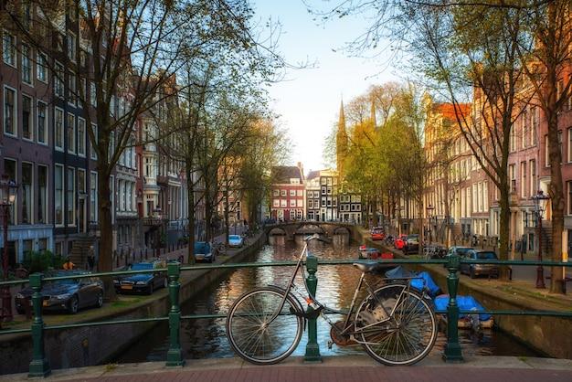オランダの伝統的な家屋とアムステルダム、オランダのアムステルダムの運河と橋の上の自転車。