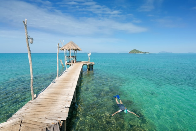 Туристы плавать в кристально бирюзовой воде возле тропического курорта в пхукете, таиланд. лето, отпуск, путешествия и отдых и отдых и путешествия на море концепции.