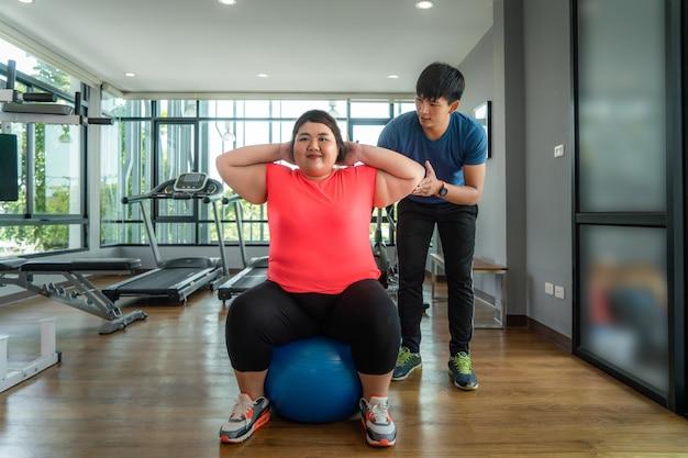 Два азиатских тренер мужчина и полная женщина, работающ с мячом в современном тренажерном зале, счастливым и улыбаться во время тренировки толстые женщины заботятся о здоровье и хотят похудеть.