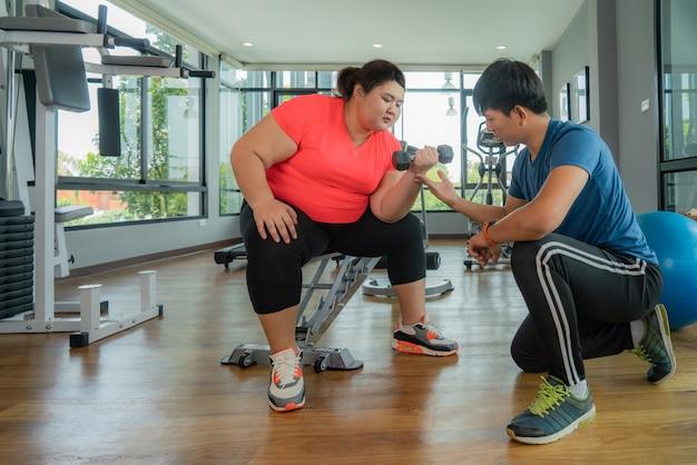 Два азиатских тренер мужчина и полная женщина, работающ с гантелями вместе в современном тренажерном зале, счастливым и улыбаться во время тренировки. толстые женщины заботятся о здоровье и хотят похудеть.
