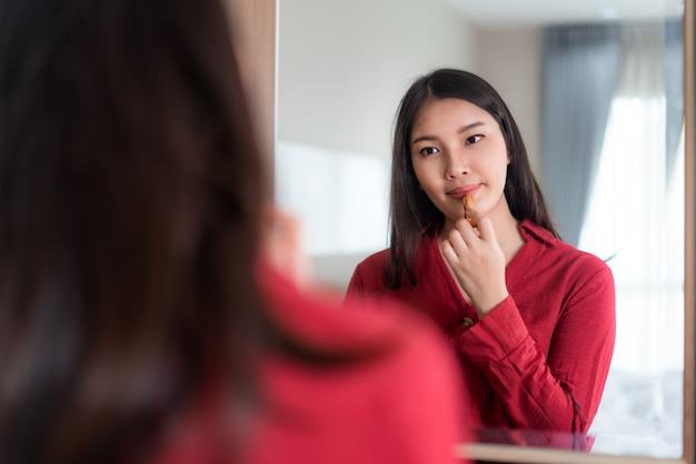 Красивая азиатская женщина нося красный цвет одела кладущ губную помаду смотря в зеркале в ее спальне дома. макияж по утрам готовлюсь перед выходом на работу.