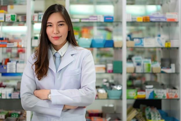 Уверенно азиатский молодой женский аптекарь с симпатичной дружелюбной улыбкой стоя сложа руки в аптеке аптека. медицина, фармацевтика, здравоохранение и люди концепции.