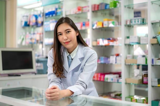 Уверенно азиатский молодой женский аптекарь с склонностью симпатичной дружелюбной улыбки стоящей на столе в аптеке фармации. медицина, фармацевтика, здравоохранение и люди концепции.