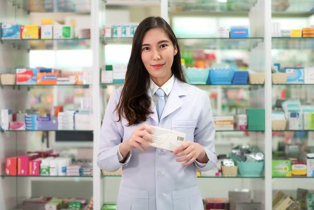 Азиатский аптекарь молодой женщины при симпатичная дружелюбная улыбка держа коробку медицины в аптеке фармации. медицина, фармацевтика, здравоохранение и люди концепции.