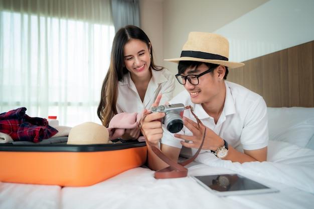 Счастливые азиатские пары распаковывая чемодан на кровати в спальне когда они приезжают в гостиничный номер и лежа и смотря фото в путешествии путешествуют на камере. азиатские рюкзаком путешествия образ жизни концепция.