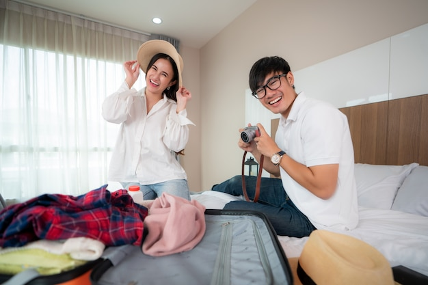 アジアのカップル旅行者が旅行休暇の準備を一緒にしたスーツケースを梱包し、旅行の準備をしているときに楽しみを探している幸せ。アジアのバックパッカー旅行ライフスタイルコンセプト。
