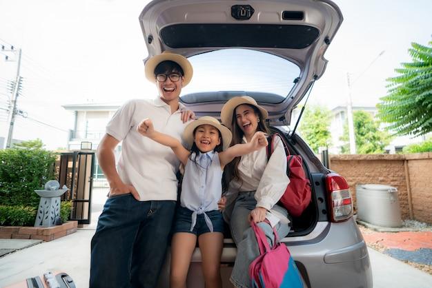 Портрет азиатской семьи с отцом, матерью и дочерью смотрит счастливым пока подготавливающ чемодан в автомобиль на праздник.