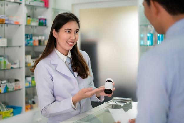 Уверенно азиатский молодой женский аптекарь с симпатичной дружелюбной улыбкой и объясняя медицину ее клиенту в аптеке аптеки. медицина, фармацевтика, здравоохранение и люди концепции.
