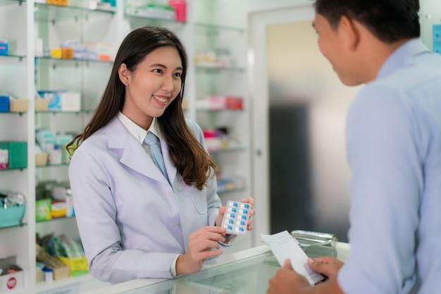 Уверенно азиатский молодой женский аптекарь с симпатичной дружелюбной улыбкой и объясняя медицину капсулы ее клиенту в аптеке аптеки. медицина, фармацевтика, здравоохранение и люди концепции.