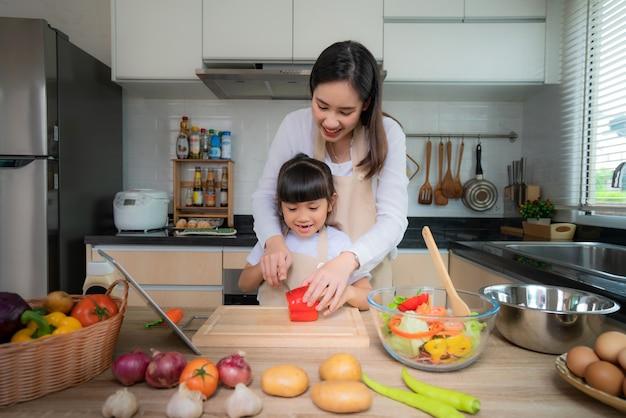 アジアの若い女性と彼女の娘はランチにサラダを調理します。