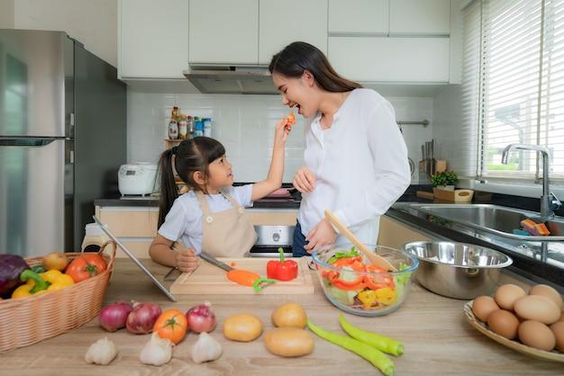 アジアの娘がランチにサラダを調理し、母親にトマトを食べさせる