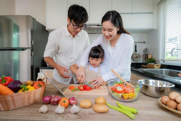 彼女の娘を教えているアジアの母は、野菜サラダを細断しました。