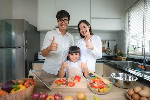 父、母、娘とアジアの家族は野菜サラダを細切りしました。