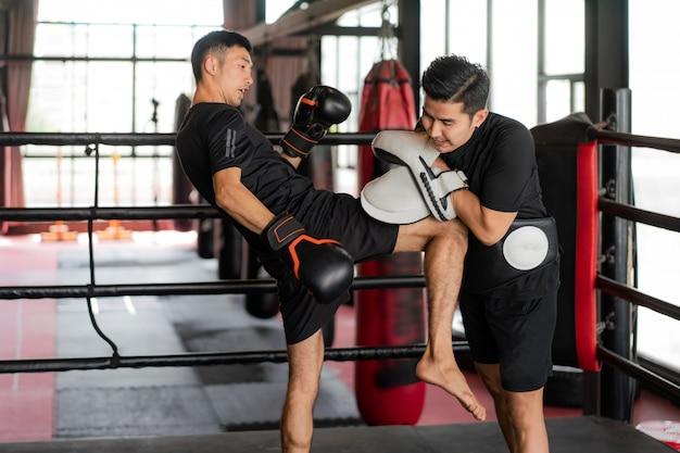 若いアジアキックボクサーは、ボクシングスタジアムでプロのトレーナーに右膝で打つ。