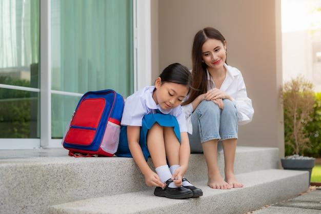 制服を着た娘の就学前の生徒が自分の靴を履いているのを見ているアジアの母。