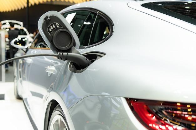 Блок питания подключается к электромобилю для зарядки от аккумулятора.