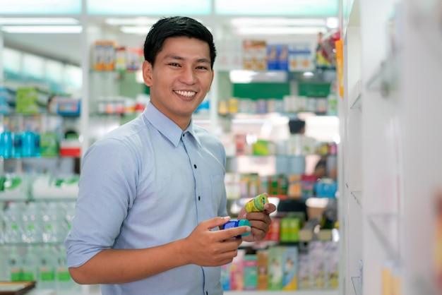 Азиатский клиент выбирая продукт и смотря камеру в аптеке фармации.