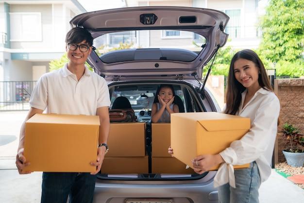 Счастливая азиатская семья с отцом и матерью стоит около автомобиля с картонными коробками и их дочерью усмехаясь в автомобиле на гараже дома.