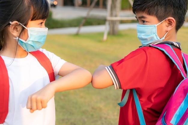 Двое азиатских детей дошкольных друзей встречаются в школьном парке вместо того, чтобы приветствовать их объятиями или рукопожатием, они бьют локтями.