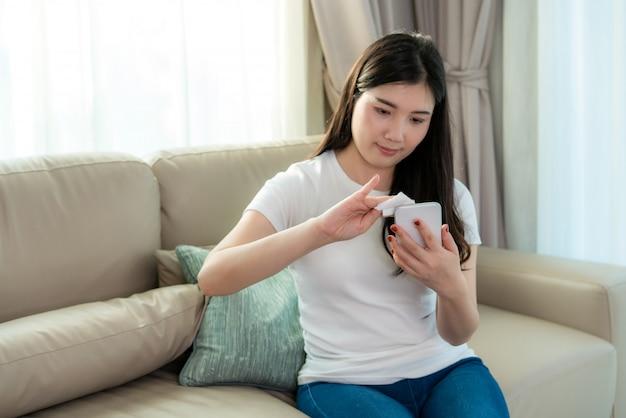 アジアの女性は携帯電話にアルコールを噴霧しています