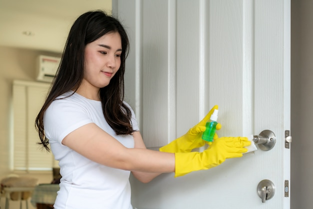 Азиатская женщина дезинфицирует дверные ручки, распыляя синее дезинфицирующее средство из бутылки
