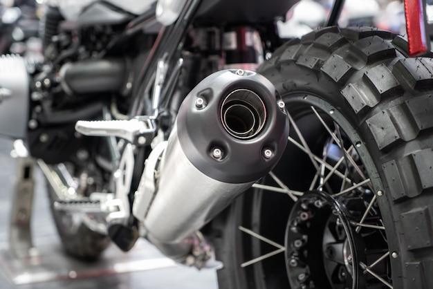 ショールームでの新しいタイヤとホイールを備えたブラックスポーツレーシングバイクの排気または吸気の拡大図。オートバイのローアングル写真。