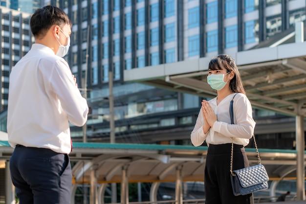 «уважай, это новое романтическое приветствие во избежание распространения коронавируса». два азиатских молодых бизнесмена и друзья встречаются в шрифте офисного здания.