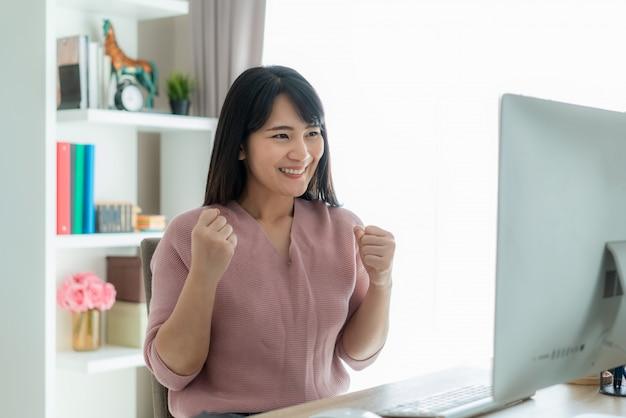 Красивая азиатская работа бизнес-леди от дома и празднует с компьютером, представлением успеха счастливым.