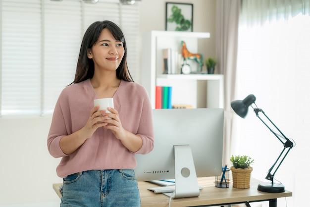 Азиатская красивая работа молодой женщины от дома работая на компьютере и выпивая кофе пока ослабьте от ее работы стоя в живущей комнате дома.