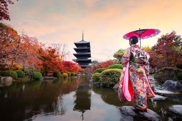 京都の秋のシーズンに木製の塔と赤いカエデの葉を持つ東寺に立っている伝統的なキミノドレスの若い日本人の女の子旅行者。