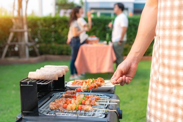 友人のグループが自宅の庭でパーティーを食べるバーベキューグリルとソーセージを調理するアジア人男性。