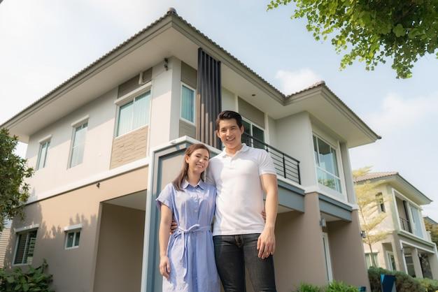 Портрет азиатских молодых пар стоя и обнимая совместно смотрящ счастливый перед их новым домом для того чтобы начать новую жизнь.