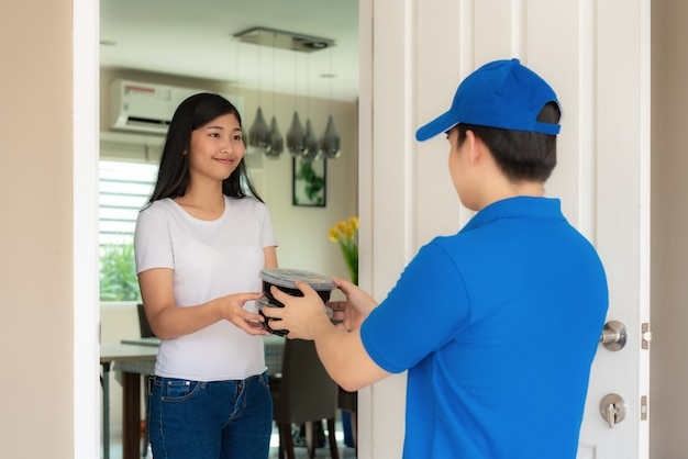 Азиатская доставка молодого человека в синей форме улыбка и проведение кучу картонных коробок в переднем доме