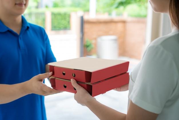 Азиатские доставки молодой человек в синей форме улыбка и проведение коробки для пиццы в передней