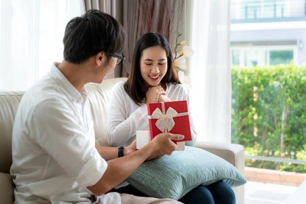 アジアの男性は女性に赤いギフトボックスを与えます。彼女は箱の中の贈り物を見て、結婚記念日や家のリビングルームでの誕生日に驚きます。