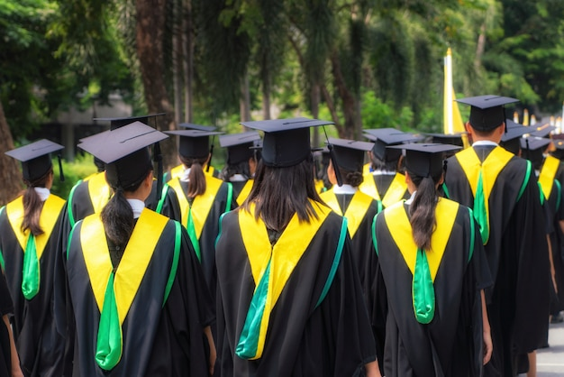 Вид сзади группы выпускников университетов в черных платьях выстраивается в степень на выпускной церемонии университета.