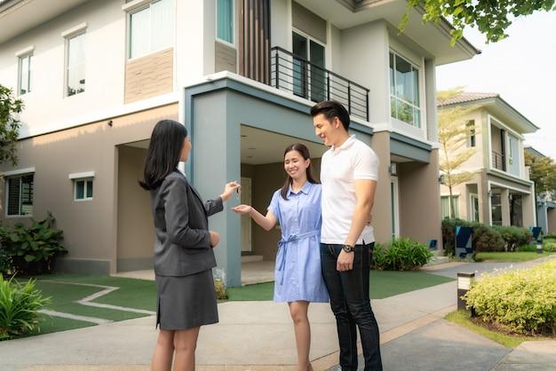 アジアの幸せな笑顔の若いカップルは、契約書に署名した後、彼らの家の前で不動産業者または全米リアルター協会加入者から鍵の新しい大きな家を取る