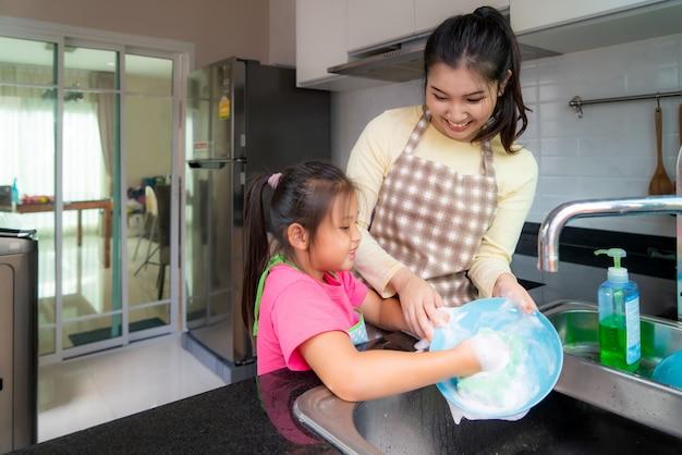 美しいアジアの母と娘が自宅の台所の流しに洗剤と一緒に皿を洗いながら楽しんでいます。