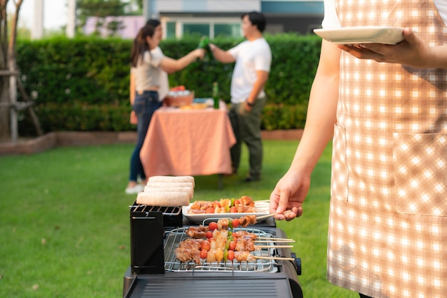 友人のグループが自宅の庭でパーティーを食べるバーベキューグリルとソーセージを調理するアジア人の男性。