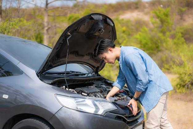 アジアの若い不幸な男が開いたボンネットの前で壊れた車のエンジンを検査して車を分解しました国の道路道路支援サービスを待っています。