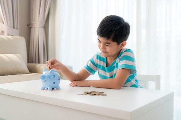Маленький азиатский мальчик вводит монету в голубую копилку в белой таблице в гостиной дома для сбережений малыша.