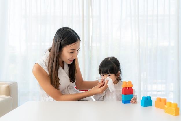 彼女の母親と一緒にナプキンに鼻水を吹いているカットされたアジアの女の子の肖像画は、彼女の鼻の近くに注意深くそれを保っています。