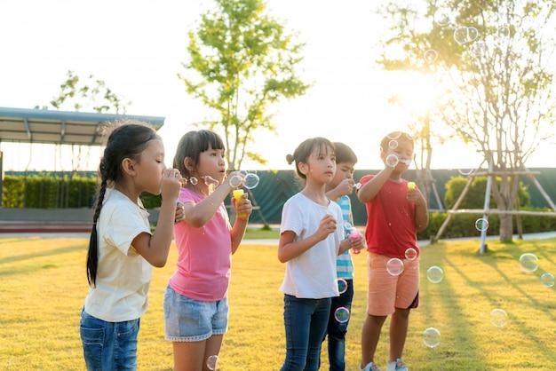 日当たりの良い夏の日に緑の芝生の上の公園で泡を吹いて一緒に遊んで幸せなアジア笑顔幼稚園の子供の友人の大規模なグループ。