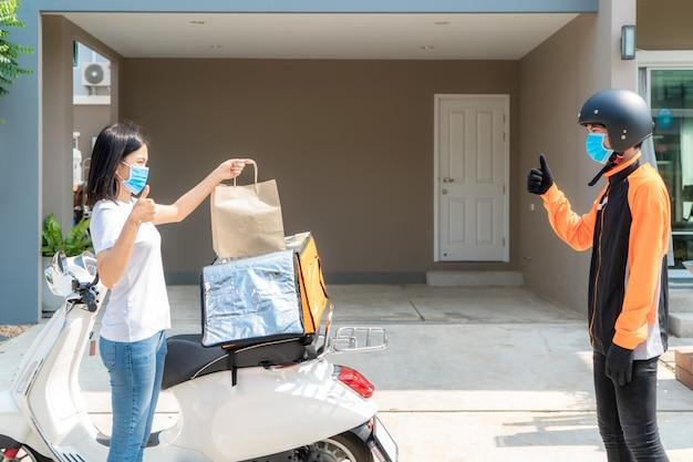 Азиатская женщина берет пакет с доставочной едой из коробки и показывает палец вверх бесконтактным или без контакта с доставщиком с велосипедом в передней части дома для социального дистанцирования от риска заражения. коронавирусная концепция