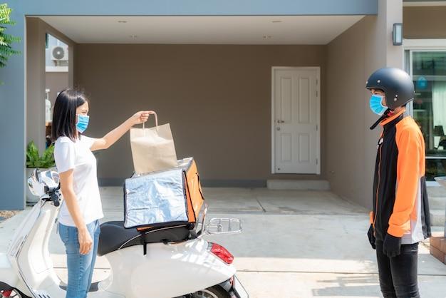 Азиатская женщина берет пакет с доставочной едой из коробки и показывает палец вверх бесконтактным или без контакта с доставщиком с велосипедом в передней части дома для социального дистанцирования от риска заражения.