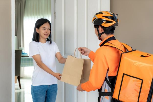 Азиатский курьер человека на велосипеде поставляя еду в оранжевой равномерной улыбке и держа мешок еды в переднем доме и азиатская женщина принимая поставку коробок от работника доставляющего покупки на дом.