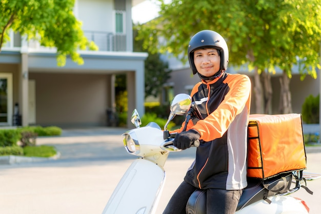 Азиатский курьер на скутере доставляет еду по улицам города с доставкой горячей еды от ресторанов и ресторанов до дома
