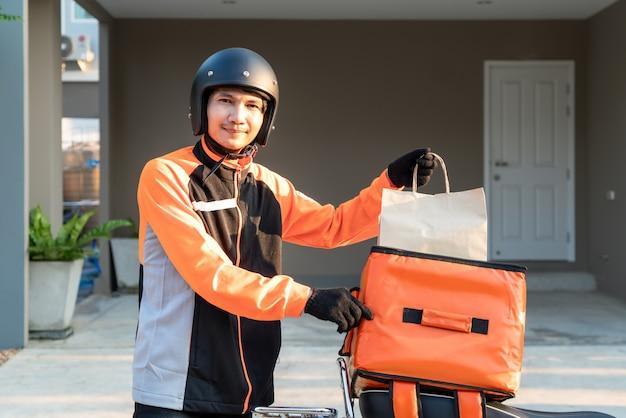 Доставка азиатский мужчина в оранжевой форме и готов к отправке с доставкой еды