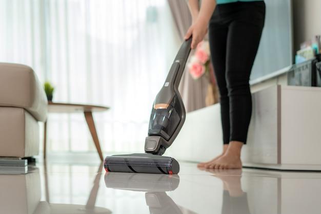 カジュアルな服を着ている女性のクローズアップは、毎日のハウスキーピングルーチンについて自由時間を使用して在宅中に自宅で掃除機を使用してリビングルームの家の床を掃除しています。