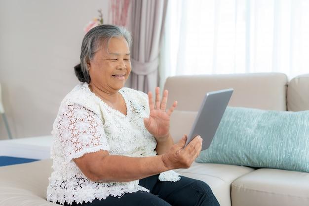 アジアの高齢者の女性の仮想ハッピーアワー会議と社会的距離を求めるビデオ通話のオンライン会議のためのデジタルタブレットでのビデオ会議で彼女の娘と一緒にオンラインで話します。